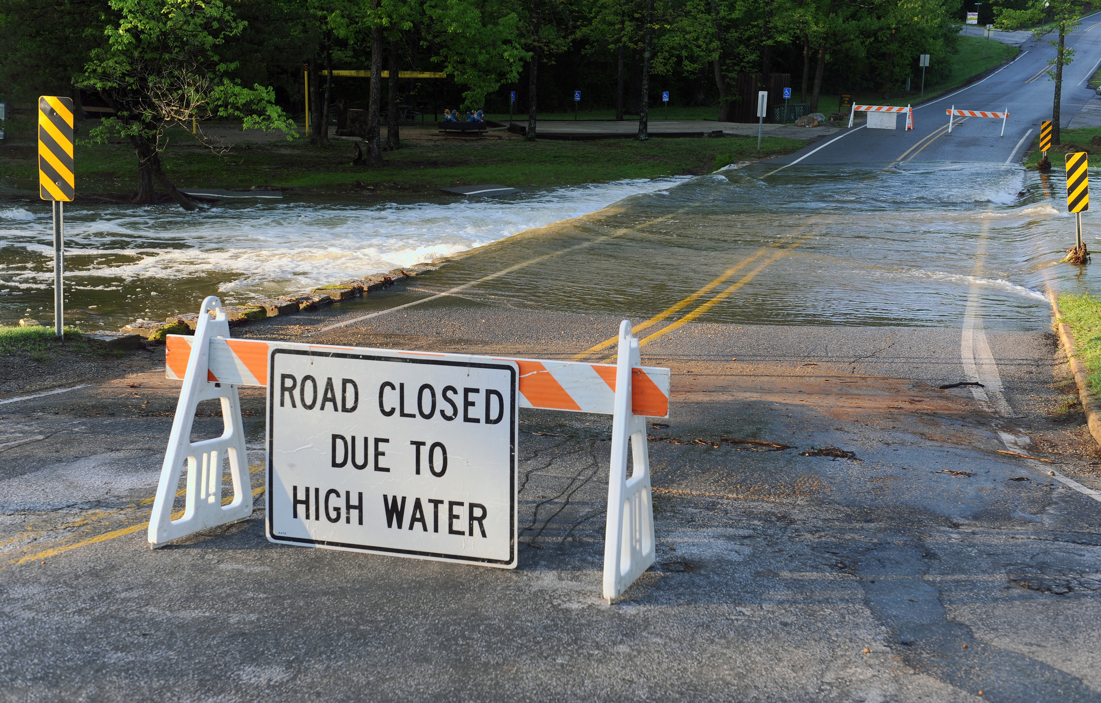 Road Closed sign due to high water in front of water crossing over the road