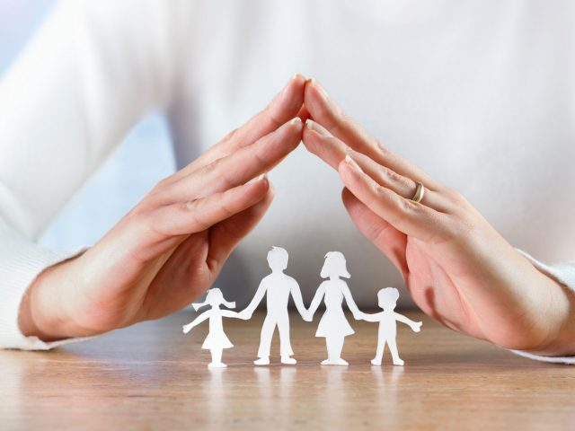 Image of hands forming a roof structure over a paper family representing protecting family at home