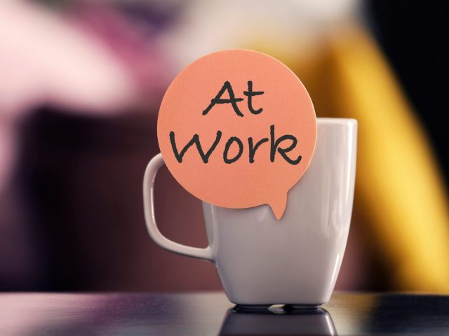 Image of a coffee cup with a sicker that says 'At Work'