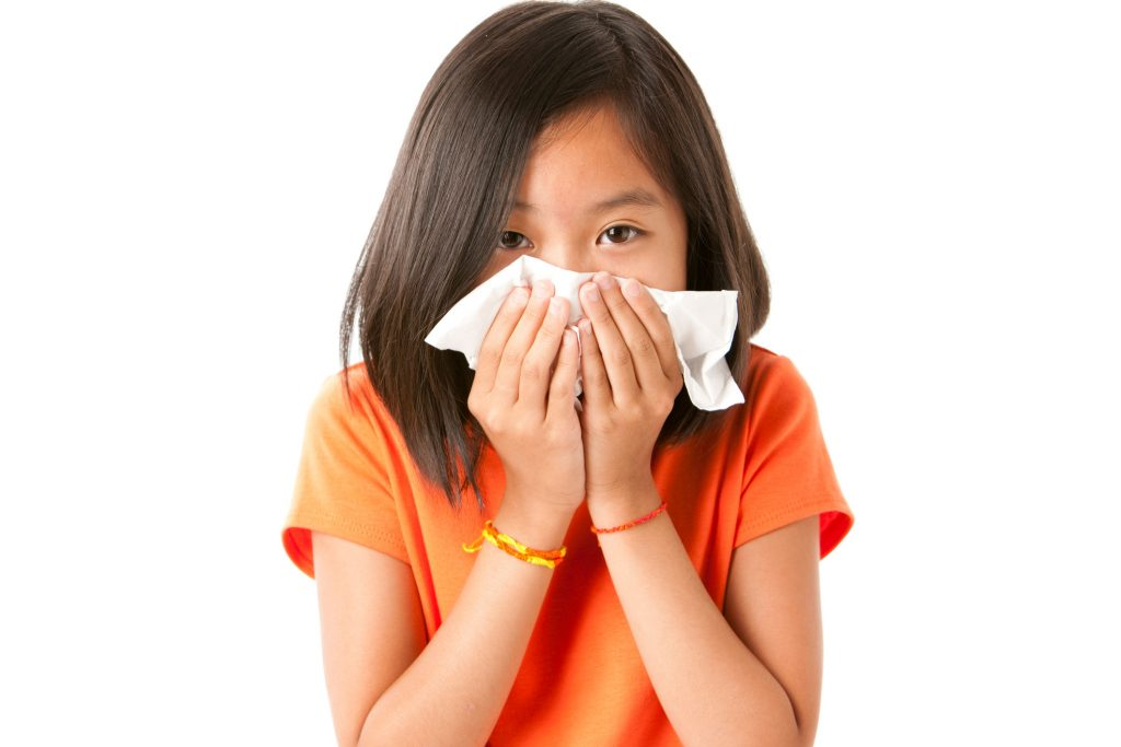 Young girl blowing her nose into a tissue
