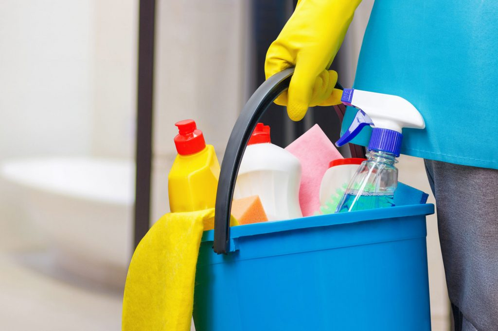 closeup of someone carrying a bucket full of cleaning equipment