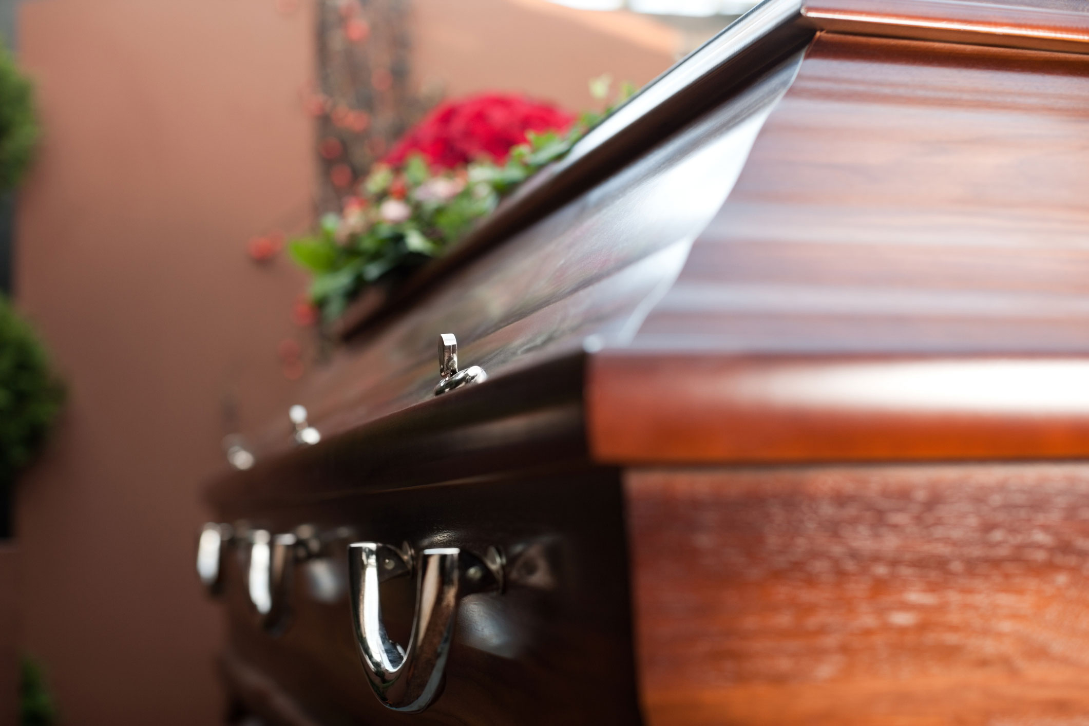 Close-up of a closed casket with red flowers on top