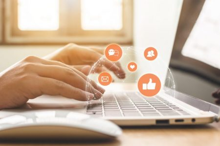 Hand of person using laptop with icon social media and social network.