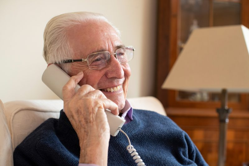 Smiling Senior Man Using Phone At Home