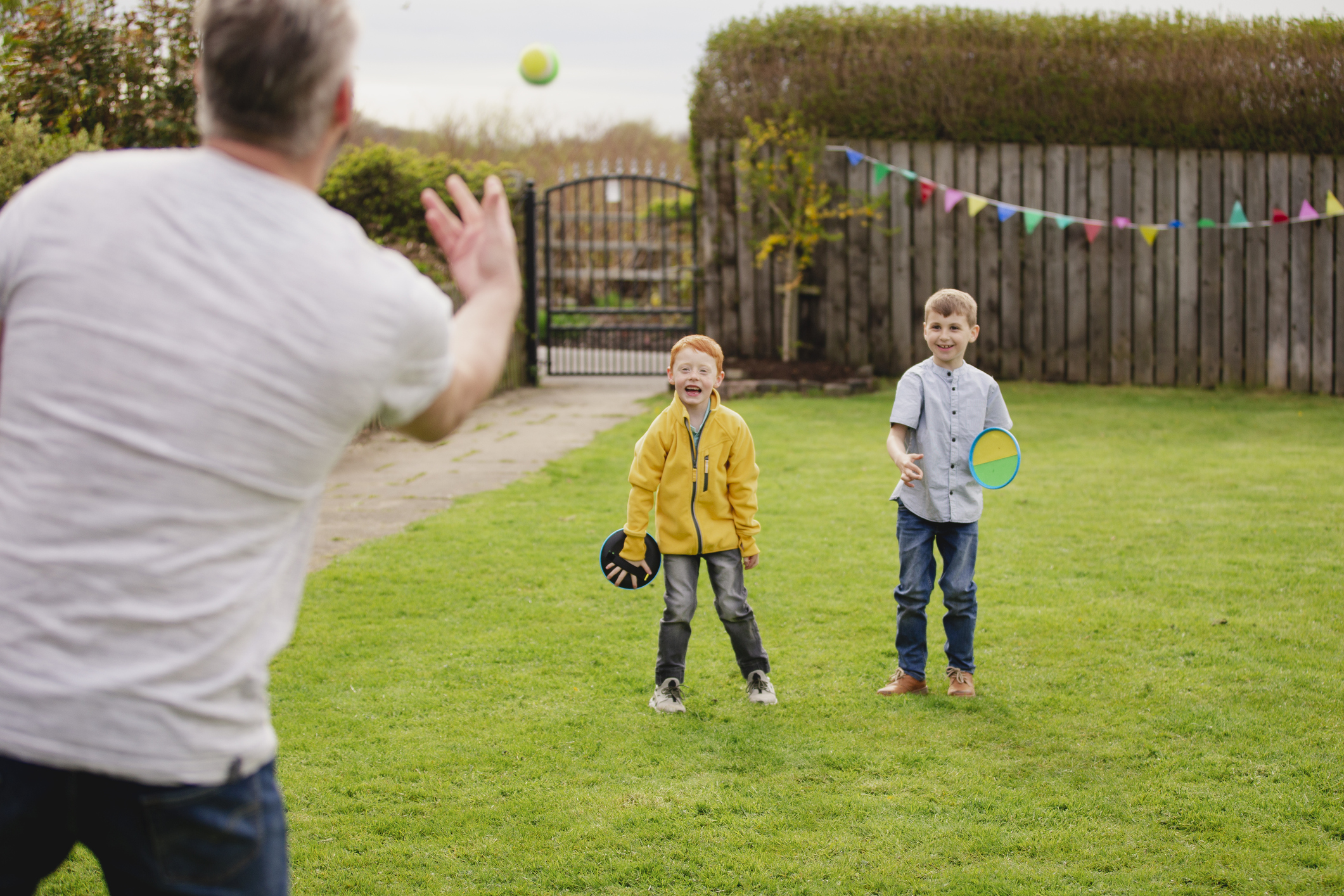 Rear view of a mid adult father throwing a tennis ball to his son and his friend. They are having fun and playing a game.
