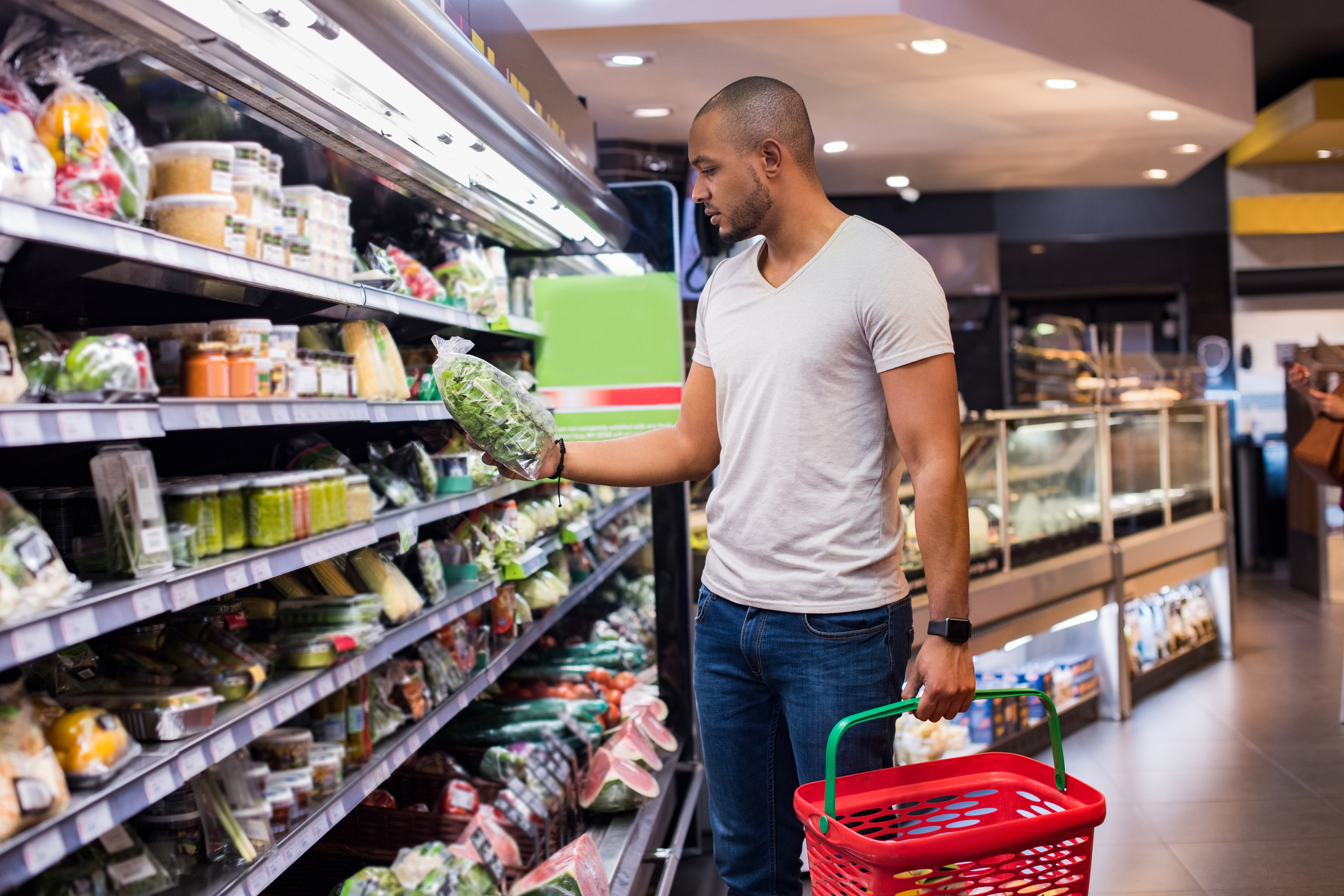 Young african man buying vegetables in grocery section at supermarket. Black man choose vegetables in the supermarket while holding grocery basket. Man shopping veggies at supermarket.