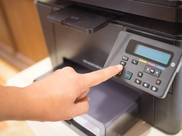 Printer Start, Finger pressing the start button on a multifunction printer or copier