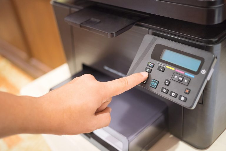 Printer Start, Finger pressing the start button on a multifunction printer or copier