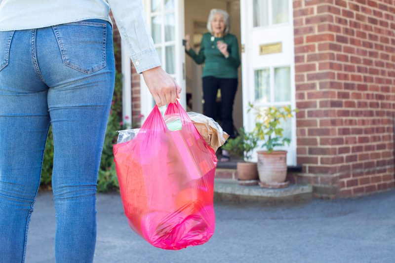 Image of a close-up of a woman carrying a bag of groceries and an elderly woman in the distance opening her door to say thank-you