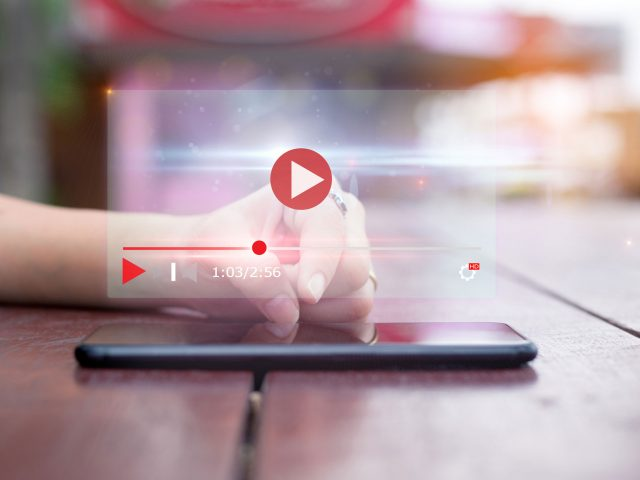 Close up image of a person using their cell phone to watch a YouTube video