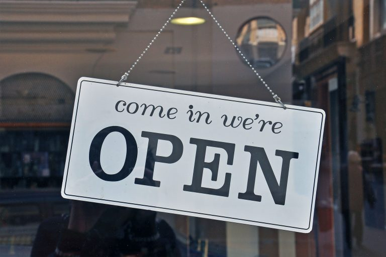 Close up of the front of a business window with a sign that says 'come in we're open'