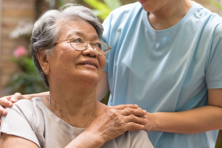 Image of an older woman looking up at a caregiver