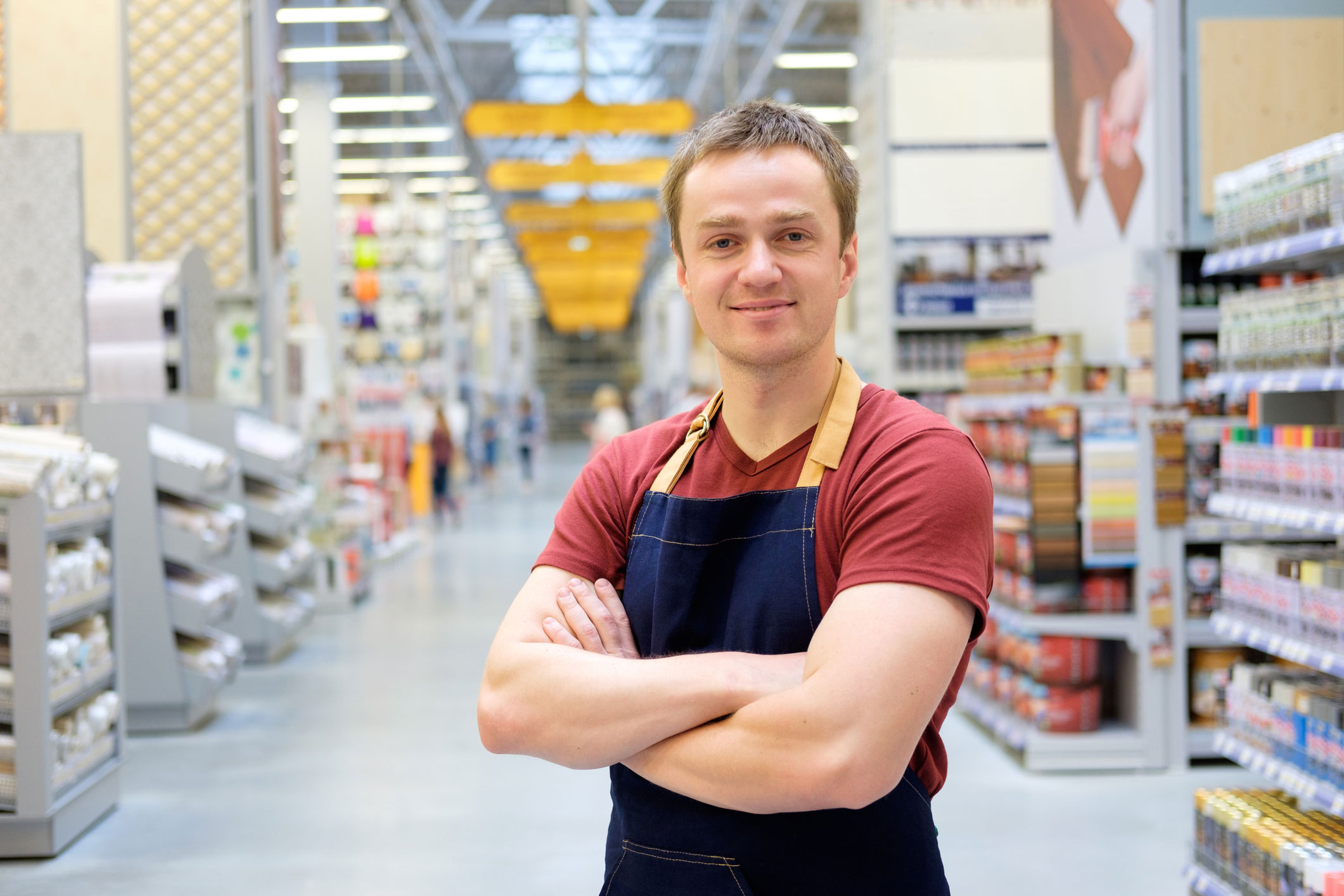 Image of a retail working standing with his arms folded in the middle of an isle of a large hardware store