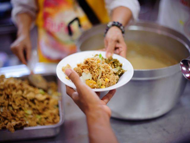 Image of a person being handed over a bowl of hot food at a homeless shelter
