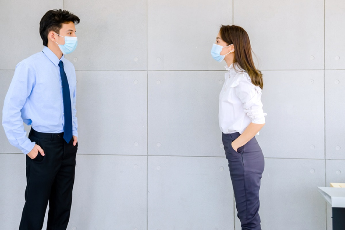 Masked co-workers practise physical distancing at work