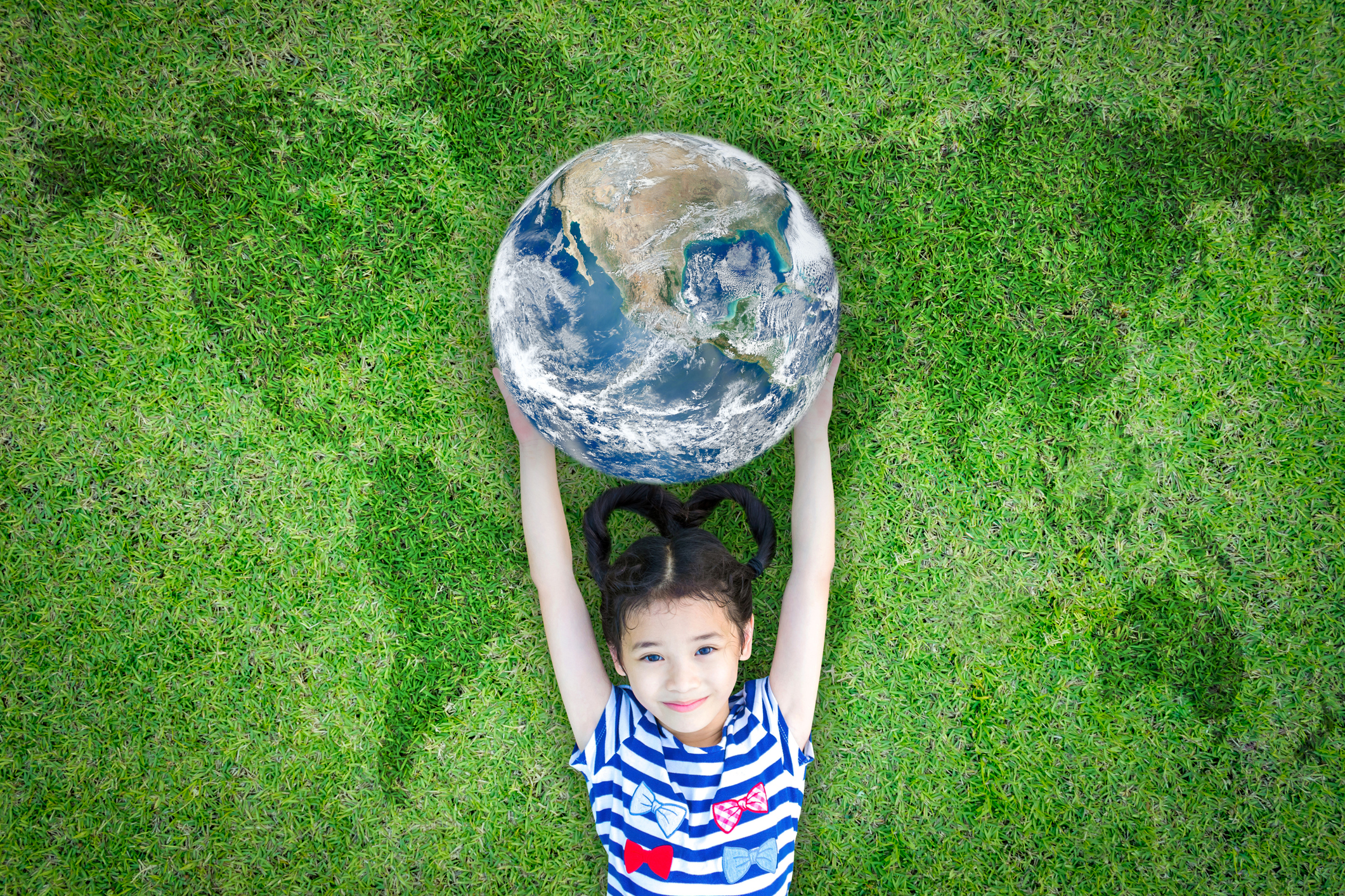 Earth day, ecological friendly and corporate social responsibility concept with kid raising world on green lawn: Element of the image furnished by NASA