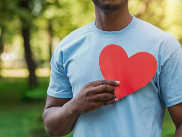 Love, volunteering and charity concept, copy space. Young black man holding red heart on his chest.