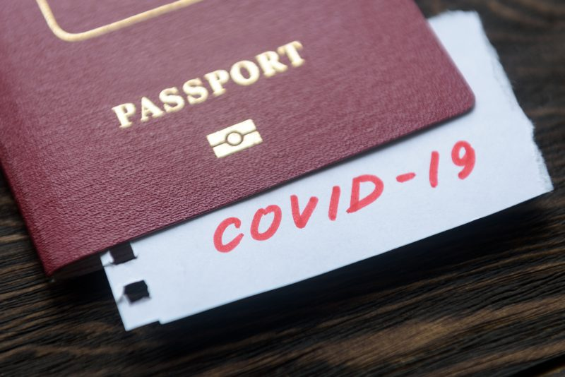 Coronavirus and travel concept. Note COVID-19 coronavirus and passport. Novel corona virus outbreak. Epidemic in Wuhan, China. Border control and quarantine of tourists infected with coronavirus.