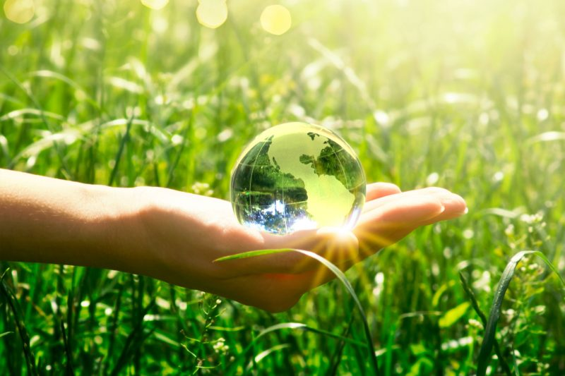 Earth crystal glass globe in human hand on fresh juicy grass background. Positive world concept.