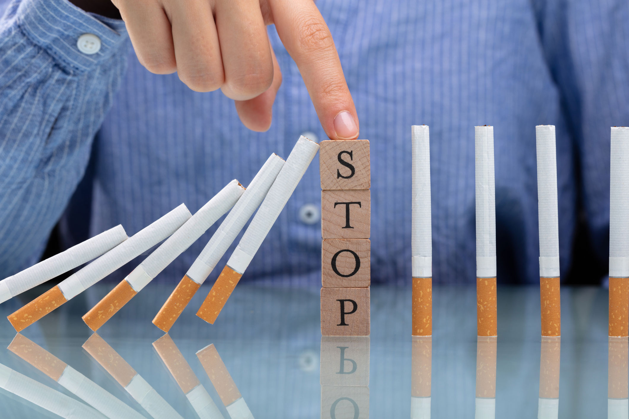 Woman Stopping Cigarette From Falling On Desk - stock photo