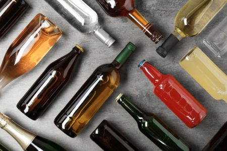 Bottles with different alcoholic drinks on grey background, flat lay - stock photo