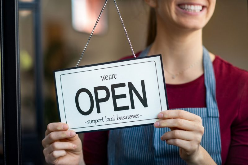 """Small business owner smiling while turning the sign for the reopening of the place after the quarantine due to covid-19. Happy businesswoman standing at her restaurant or coffee shop gate with open signboard. Close up of woman""""u2019s hands holding sign now we are open support local business."""