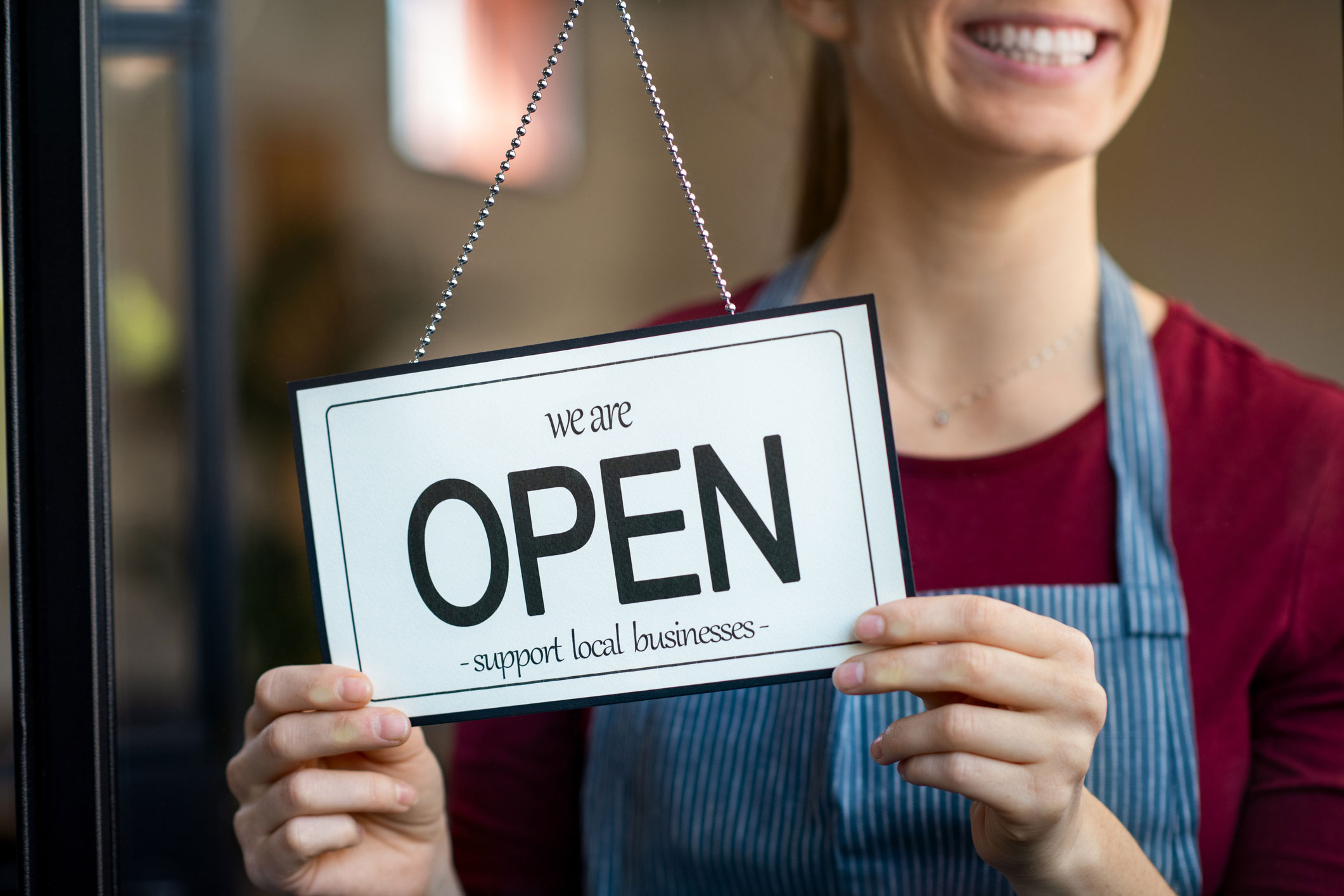 "Small business owner smiling while turning the sign for the reopening of the place after the quarantine due to covid-19. Happy businesswoman standing at her restaurant or coffee shop gate with open signboard. Close up of woman""u2019s hands holding sign now we are open support local business."