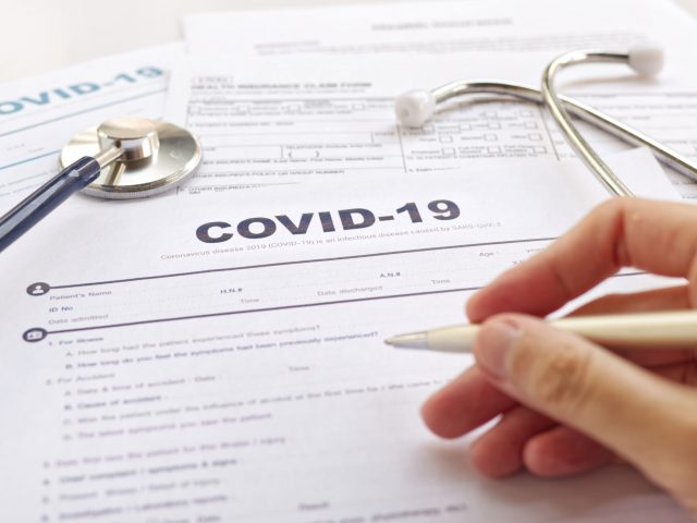 "COVID-19 Health paperwork concept. Blurring of hand holding pen and Stethoscope on health form. Focus on "" COVID-19 """