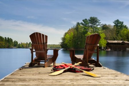 Two Adirondack chairs on a wooden dock facing the blue water of a lake in Muskoka, Ontario Canada. Canoe paddles and life jackets are on the dock. A cottage nestled between green trees is visible.