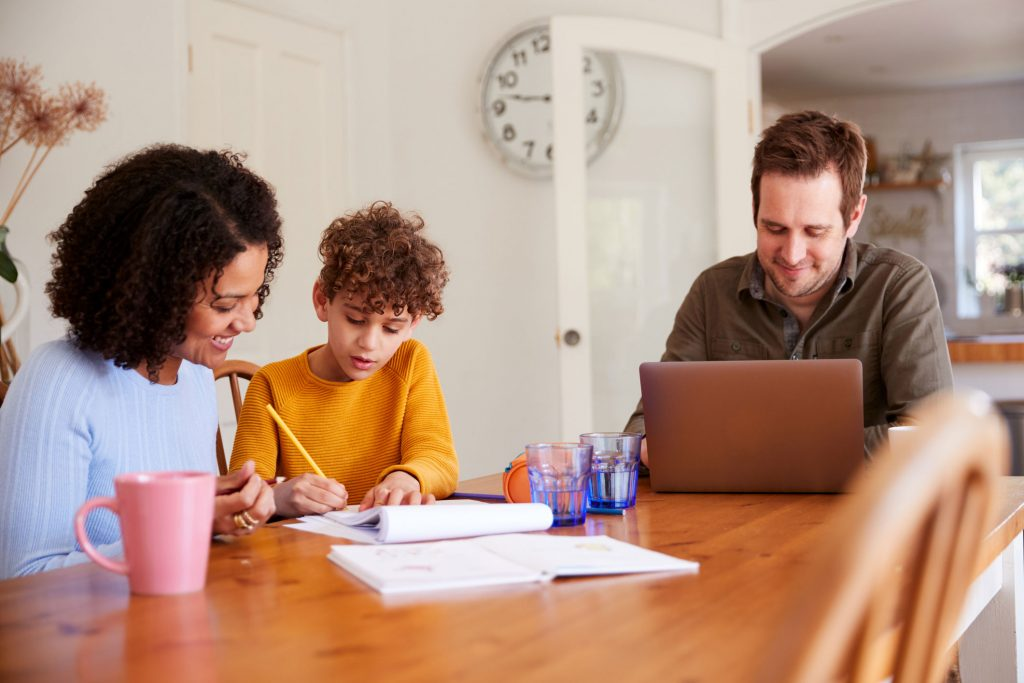 Father Works On Laptop As Mother Helps Son With Homework On Kitchen Table - stock photo