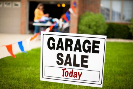 Garage sale sign on the front yard of a suburban house with a woman looking at items on a table.