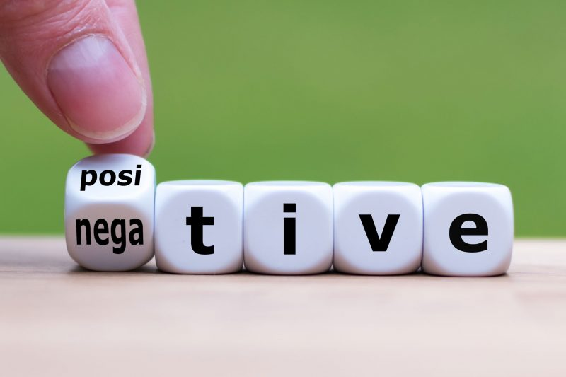 "Hand turns a dice and changes the expression ""negative"" to ""positive""."