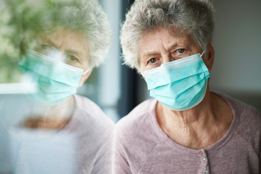 a old woman or grandma is wearing a respirator or surgical mask and looking out of the window