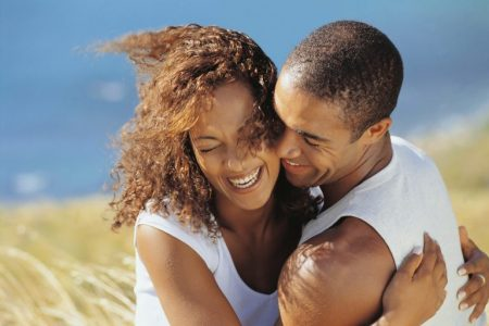 Couple smiling and hugging outdoors by a beach