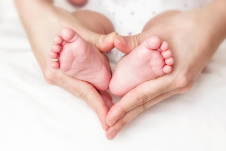 newborn baby feet in the mother's hands