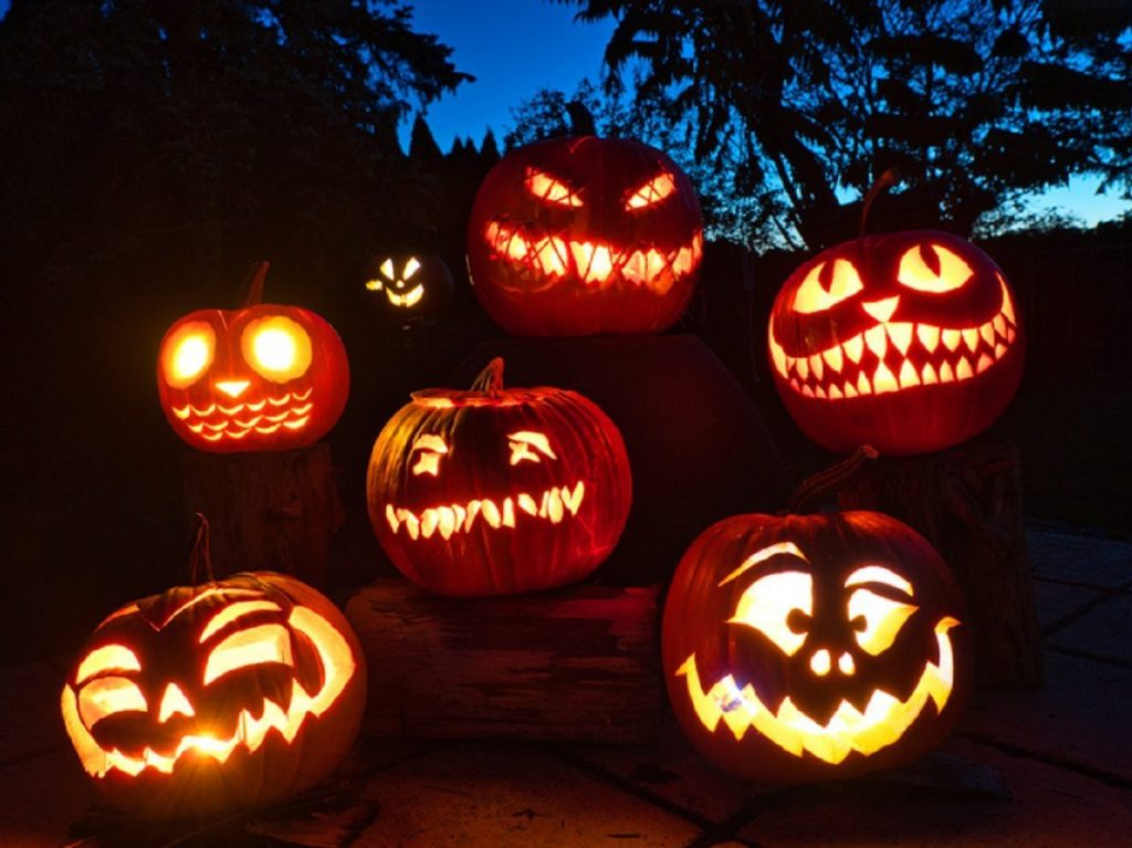 row of candle-lit Halloween pumpkins