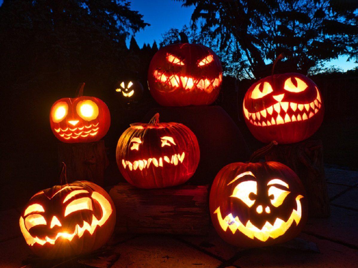 row of candle-lit Halloween pumpkins
