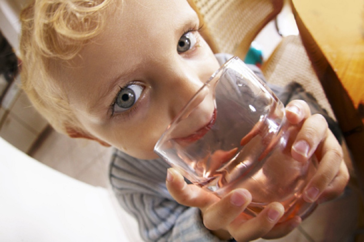 young boy holding glass of water