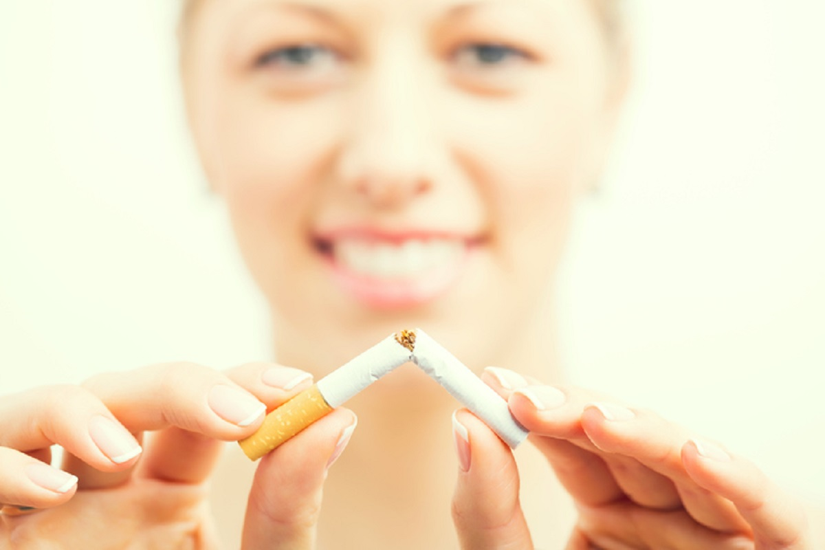 Woman smiles as she breaks a cigarette in half