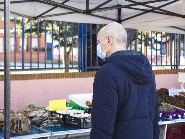 Man wearing a mask buys mushrooms at a local farmers' market